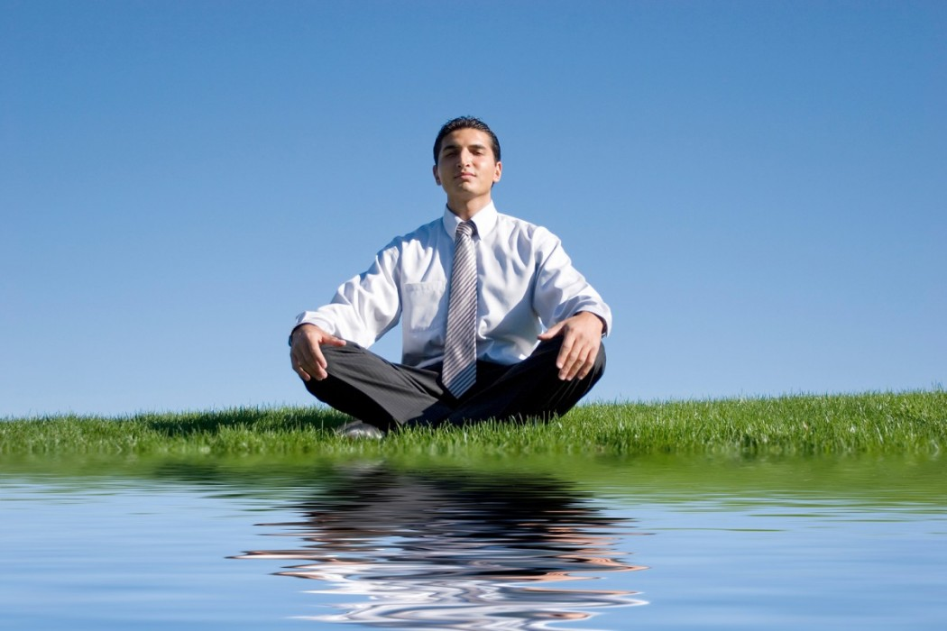 Businessman-meditating-on-gree-11897501